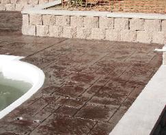 stamped concrete pool deck with interlock wall